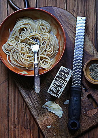 Brown bowl with pasta and fork. Wedge of cheese, microplane and pepper in bowl all on cutting board.