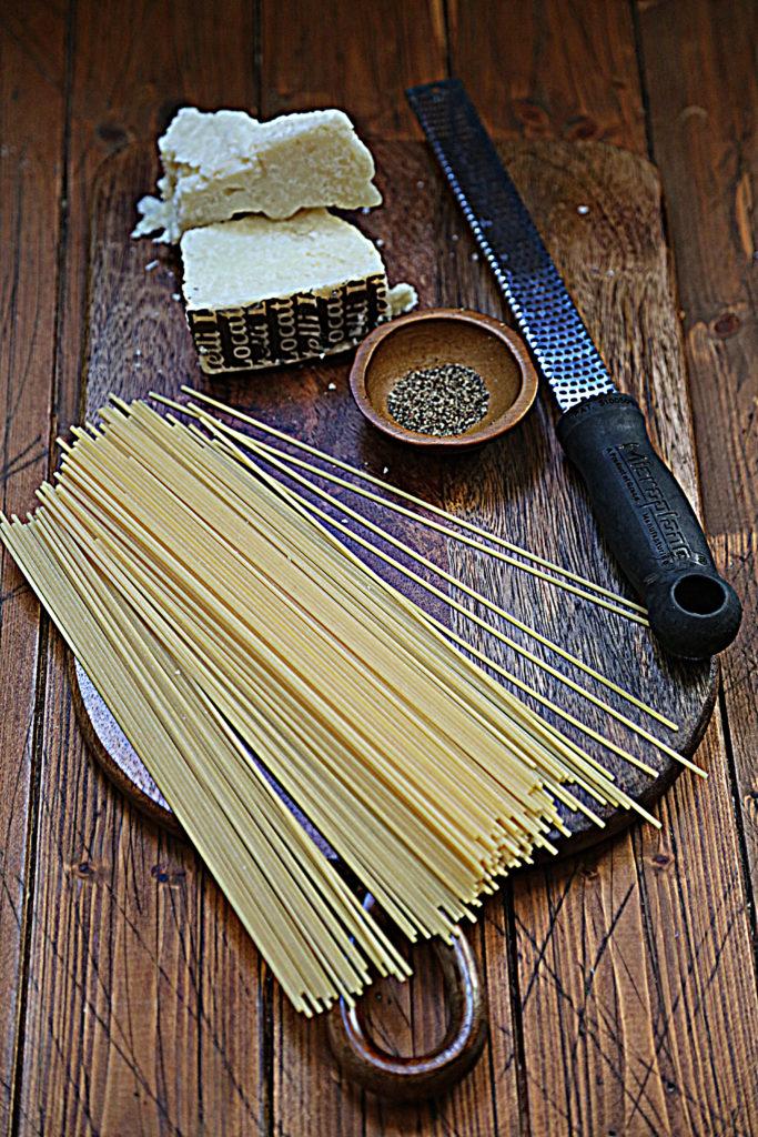 spaghetti, microplane, small wooden bowl of pepper, wedge of pecorino sitting on cutting board.