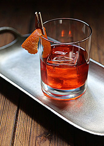 negroni cocktail with orange peel on silver tray.