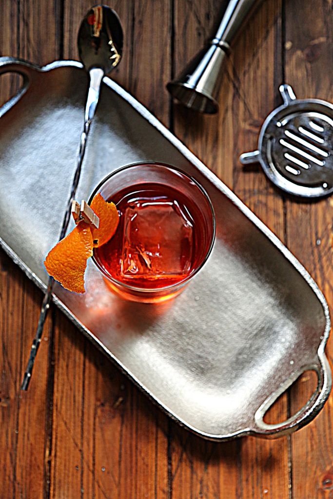negroni cocktail on silver tray with bar spoon. Strainer and jigger to side.