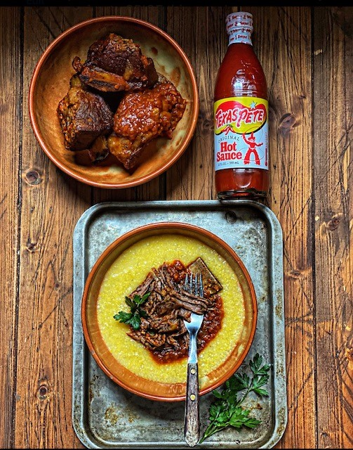 Brown bowl of braised short ribs, bottle of hot sauce. Baking sheet with bowl of creamy polenta, shredded ribs and fork.