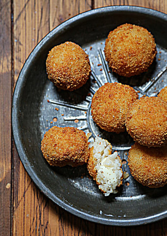 close up of fried arancini balls in metal pie plate.